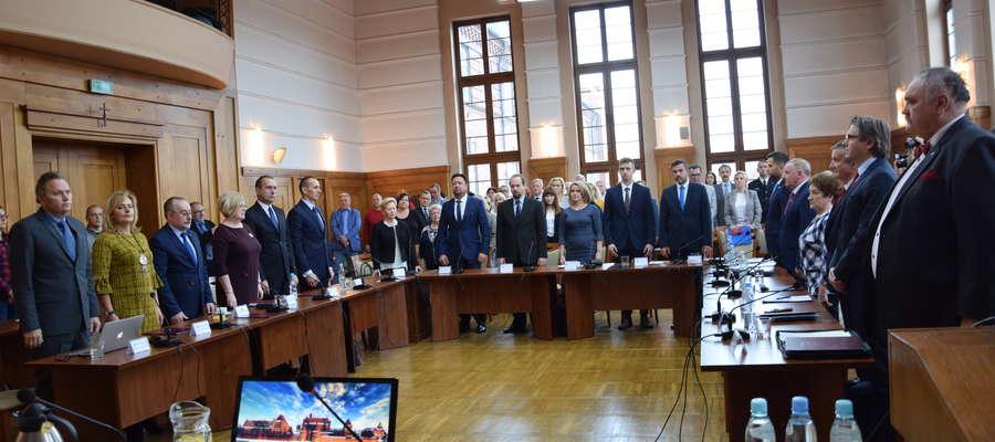 na zdjęciu widać radnych Rady Miasta Malborka stojących przy stołach w Sali Posiedzeń
