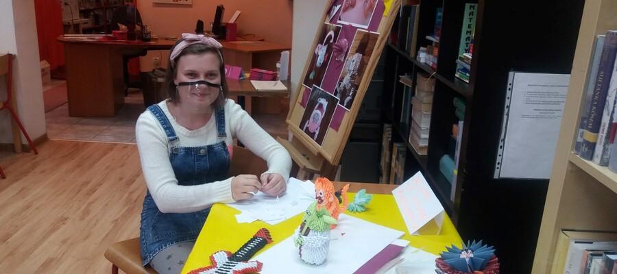 na zdjęciu widać uczennicę siedzącą w bibliotece przy stole ze swoimi pracami