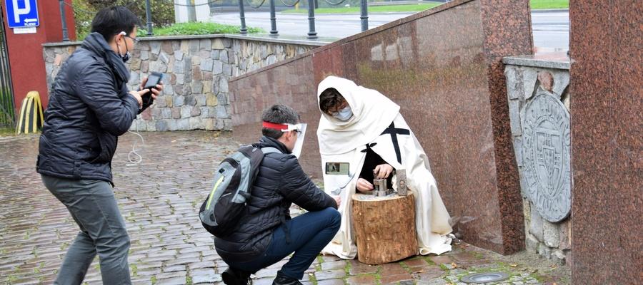 na zdjęciu widać osoby nagrywające mincerza w stroju krzyżackim