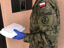 na zdjęciu widać żołnierza PBOT z pojemnikiem na posiłek