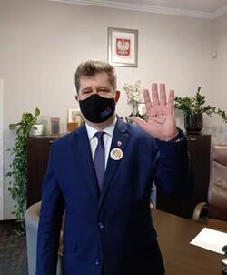 na zdjęciu widać burmistrza z namalowaną uśmiechniętą buźką na dłoni