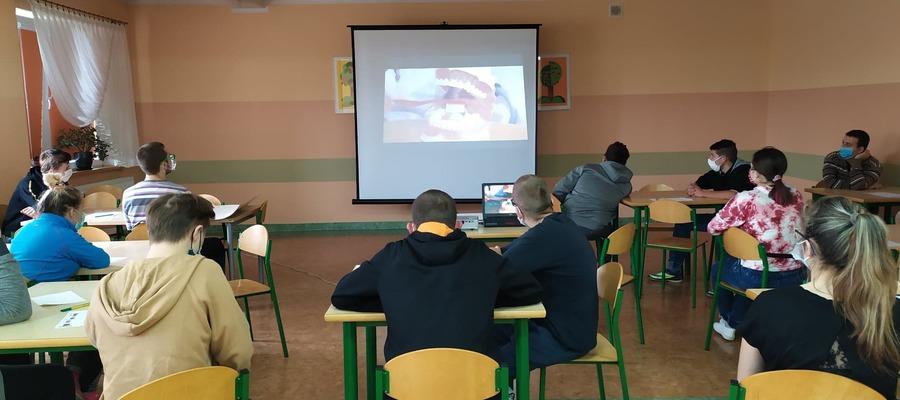na zdjęciu widać podopiecznych siedzących w ławkach w klasie
