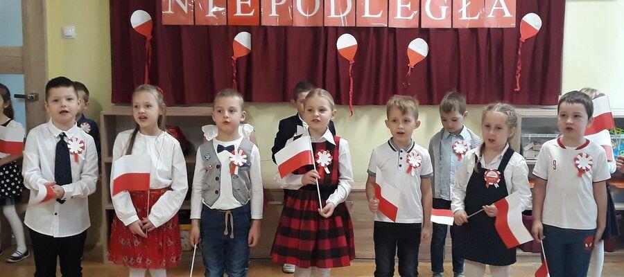 """na zdjęciu widać dzieci z flagą Polski i napisem w tle """"Polska Niepodległa"""""""