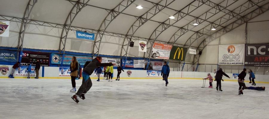 na zdjęciu widać osoby jeżdżące na łyżwach na lodowisku