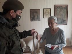 na zdjęciu widać żołnierza 7 PBOT wręczającego paczkę seniorce