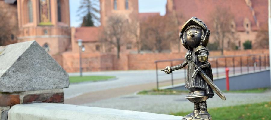 na zdjęciu widać figurkę Marianka na tle zamku