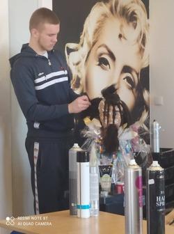 uczeń wykonujący fryzurę na manekinie