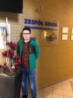 Kamil Kot na tle loga szkoły