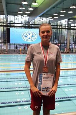 Nadia Walentynowicz z medalem i dyplomem na basenie
